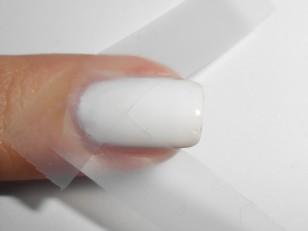 Gdy biały lakier jest już w zupełności suchy naklej dwa kawałki taśmy tak, aby utworzyć kształt trójkąta przy końcówce paznokcia