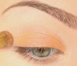 Całą powiekę pomaluj pomarańczowym, opalizującym cieniem.