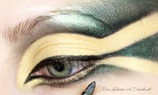 Górną linię rzęs maluję czarnym eyelinerem i wyciągam kreskę w wewnętrznym kąciku oka. Dolną czarna kreskę rozcieram ciemnozielonym cieniem z brokatem, kierując się w dół. Maluje linię wody w oku na czarno.