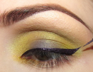 Fioletowym eyelinerem w żelu maluję stanowczą kreskę na górnej powiece zakańczając ją 'jaskółką'.