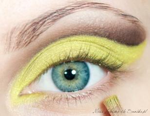 Precyzyjnym pędzelkiem wyciągam żółty kolor w szpic, wzdłuż wcześniej nałożonego brązu w zewnętrznym kąciku oka. Obrysowuję również wewnętrzny kącik.