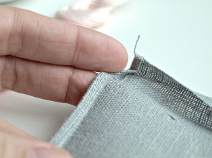 Żelazkiem przeprasowujemy dwukrotnie podwinięte brzegi ( górny po 1cm , boczne po 0,5 cm)