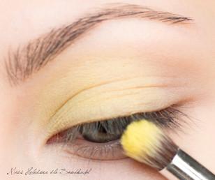 Na powiekę nakładam bazę pod cienie. Makijaż zaczynam od pokrycia wewnętrznego kącika górnej powieki żółtym, matowym cieniem zmieszanym z bielą i rozcieram go w kierunku środka powieki.