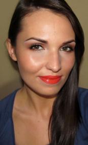 Na szczyty kości policzkowych nałóż rozświetlacz, a twarz wykonturuj bronzerem; muśnij nim również policzki aby dodać im koloru. Na usta nałóż pomadkę w intensywnym pomarańczowym kolorze.