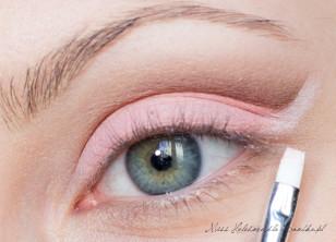 Wzdłuż wcześniej wyznaczonej brązowej linii w zewnętrznym kąciku oka, maluję białą kreskę, która wizualnie stanowi przedłużenie linii dolnej powieki. Białą kredkę wzmacniam białym, matowym cieniem.