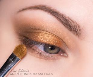 Na środek powieki naóż wilgotnym pędzelkiem pomarańczowo-złoty cień.